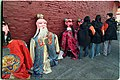 Giant statutes of Taoist deities rest against wall with young volunteers nearby.jpg