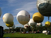 Many white and yellow gas balloons taking off from a grassy field.