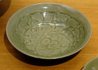A grey-green shallow bowl or curved plate with a large orchid design painted into the inside of the bowl.