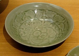 Yaozhou ware - A typical Yaozhou design of scrolling foliage, accentuated by pooling of the glaze in the moulded depressions. Compare the carved bowl above.