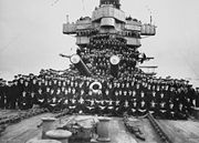 A large number of men posing for a photo on the foredeck of a warship. Two of the ship's gun barrels are visible in the middle of the group.