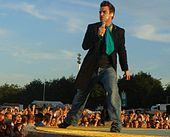Colour photograph of Robbie Williams performing live on stage in 2006.