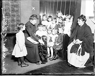 Northwestern University Settlement House - Harriet E. Vittum holding book, Northwestern University settlement house children gathered around, 1914