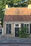 foto van Huisje zonder verdieping onder pannen zadeldak, links tegen een puntgevel gebouwd