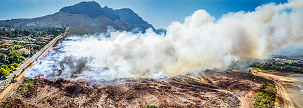 An aerial view of a controlled burn in Helderberg Nature Reserve in South Africa bordering the city of Cape Town. In South Africa controlled burns are important for maintaining the ecological health of indigenous fynbos as well as reducing the intensity of future burns.