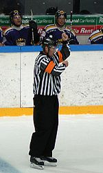 An referee signals a penalty for high sticking