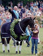 Hubertus Schmidt sitzt auf einem dunkelbraunen Dressurpferd. Dieses trägt einen grünen Siegerkranz um den Hals. Schmidt hat seinen Zylinder vom Kopf genommen und zeigt mit diesem in Richtung des Publikums. Er trägt eine hellblaue Siegerschärpe.