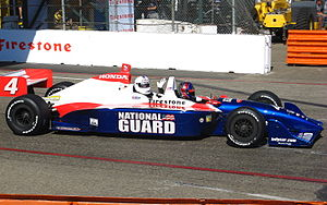 Huell Howser - Howser riding in a tandem INDYCAR race car at the 2009 Long Beach Grand Prix