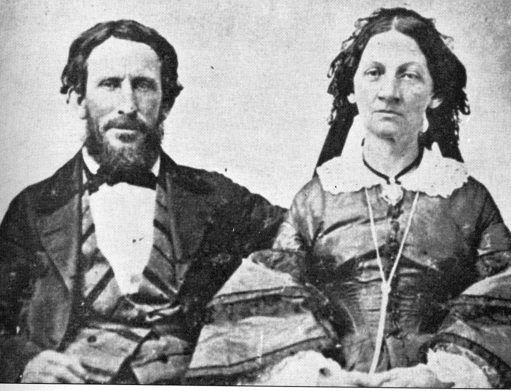 He has dark bushy hair and a beard and is wearing a three-piece suit with wade lapels and a bow tie. She has dark hair and wears a 19th-century dress with lace collar and bell sleeves.