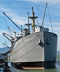 "Photograph of the liberty ship SS ""Jeremiah O'Brien"" at dock, cranes bristling along its length. A banner on a nearby fence reads ""Open"", indicating its status as a museum ship."