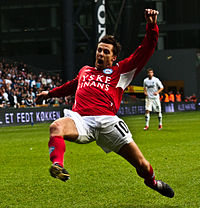 A photograph of a man dressed in a red football sweater, white sport shorts and red socks. The man is in mid play during a football match throwing himself forward for something or someone who is off-picture.