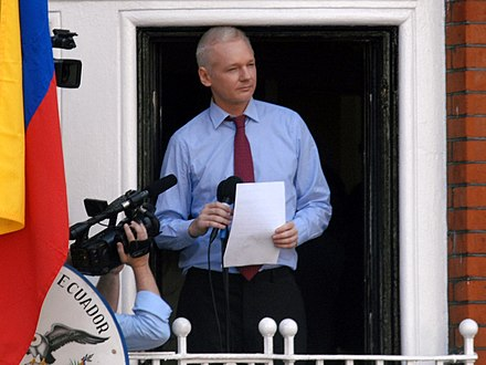 Assange on balcony of Ecuadorian embassy in London in 2012 Julian Assange in Ecuadorian Embassy cropped.jpg