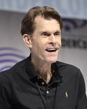 A photograph of Kevin Conroy speaking at a convention