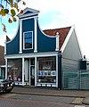 foto van Houten huis, voorzien van een ingezwenkt voorschot met pilasters en fronton