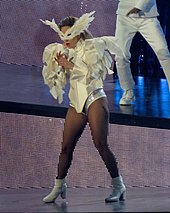 Gaga in a white bodysuit with large sleeves and a feathered mask.
