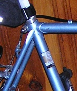 Lugged steel frame construction - This seat lug joins the seat tube, top tube, and seat stays of a steel touring bicycle frame.  It also has an opening in which to insert the seat post, and a clamp to hold the seat post securely in place.