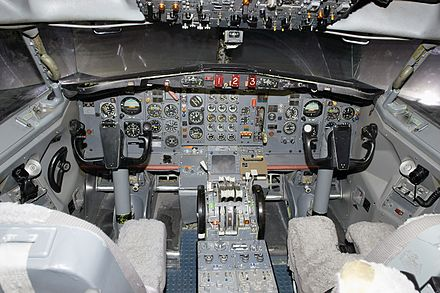 The nose gear steering-wheel (tiller) is visible as a semi-circular wheel to the left of the yoke in this photo of a Boeing 727 cockpit - Rudder