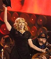 A blond woman in a black dress, holding a black hat atop her head with her riht hand, and a microphon in her left. She is pointing her tongue towards the camera. Beside her the smiling face of a man is visible.