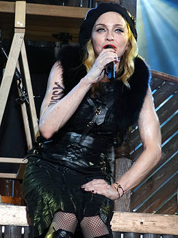 A blond woman dressed in black singing to a microphone.