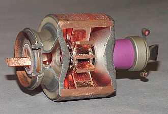 Cavity magnetron - Magnetron with section removed to exhibit the cavities. The cathode in the center is not visible. The waveguide emitting microwaves is at the left. The magnet producing a field parallel to the long axis of the device is not shown.