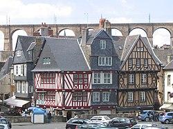 Maisons médiévales à colombages et ardoises, sur fond de viaduc ferroviaire.