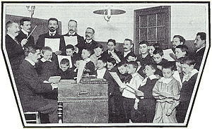 Henri O'Kelly - Henri O'Kelly (far left) conducting a rehearsal of the choir of St-Vincent-de-Paul (1903). Source: Musica, January 1904.