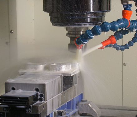 A milling machine in operation, including coolant hoses. Makino-S33-MachiningCenter-example.jpg