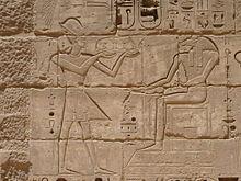 Hulp van een man met een kroon die een dienblad met voedsel vasthoudt voor een zittende man met het hoofd van een ram