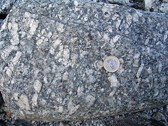 Phenocryst - Granites often have large feldspathic phenocrysts. This granite, from the Swiss side of the Mont Blanc massif, has large white plagioclase phenocrysts, triclinic minerals that give trapezoid shapes when cut through). 1 euro coin (diameter 2.3 cm) for scale.