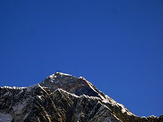 Hillary Step - In this pre-2015 view of Mt. Everest, the high point is the summit; to the right of the summit, the southeast ridge slopes down to the Hillary Step, and then rises up to the South Summit. This is looking at the Step from the West looking east to its side