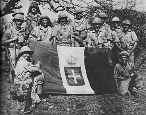Kenya in World War II - South African troops in Moyale, Kenya pose with an Italian flag captured after retaking the town from Italian forces in early 1941.