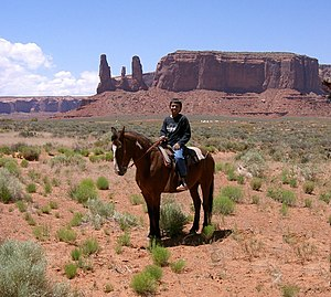 Four Corners - A young Navajo boy on horseback in Monument Valley. The Navajo Nation includes much of the Four Corners area, including the valley, used in many western movies.