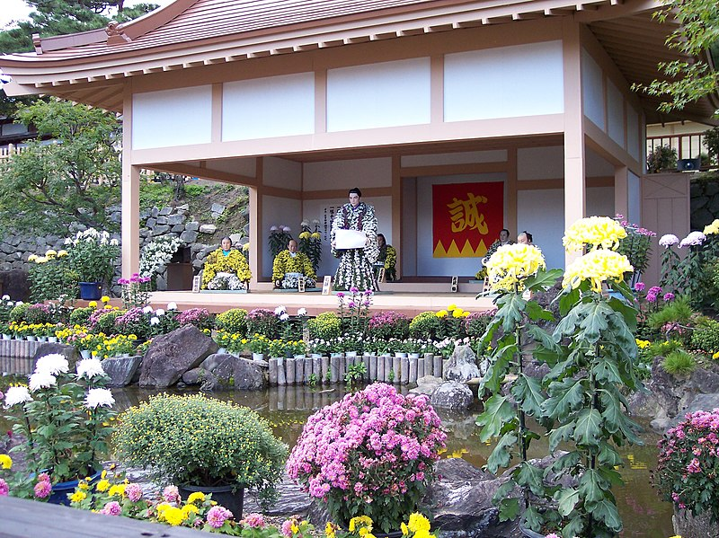Life-size manikins dressing in traditional clothing made of chrysanthemums sit in temple.