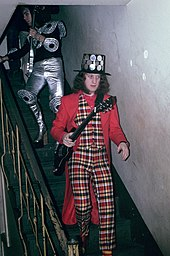 A man walks down a flight of stairs. He holds a guitar and wears a black hat studded with round metal plates. His vest and pants are chequered. His coat and shirt are plain red. His socks are striped.