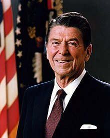 A man in his 70s, with black gelled hair parted on the right, wearing a dark suit and spotted tie, smiling; flags, including the Stars and Stripes, in the background