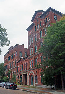 "A large brick building, five stories on the right, three in the middle and four on the right, seen from across a cobblestone street. On the pediment atop the left, the words ""Hinckel Brewing Company"" can be seen."