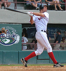 A man in a white baseball uniform and red socks swings left-handed at a baseball.