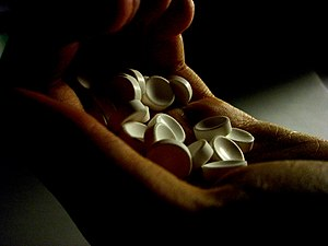 a hand holding unidentified white pills