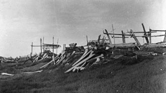 Tikiġaġmiut - Semi-underground men's community house (Qargi) with bowhead whale bones, Point Hope, Alaska, 1885