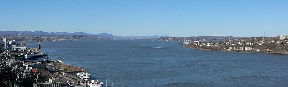Where the Saint Lawrence River narrows, between Quebec City (left foreground) and Lévis (seen at right). The Île d'Orléans appears in the central distance.