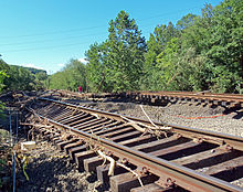 Two sets of railroad tracks twisted and tilted, with some woody debris on and around them
