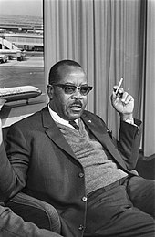 A middle-aged black man in a suit, seated in an airport lounge with a cigarette