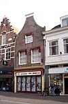 foto van Huis met eenvoudige halsgevel, onder tot winkel verbouwd. Van belang voor nr 45