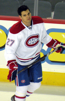 "A hockey player with short dark hair looks to his right as he skates.  He is in a white uniform with red and blue trim, the number 27 on his arms and a stylized ""CH"" logo on his chest."