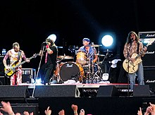 The Red Hot Chili Peppers performing on stage in 2006. From left to right: Flea is playing a bass guitar, Anthony Kiedis is singing, Chad Smith is playing a set of drums and John Frusciante is playing a guitar.