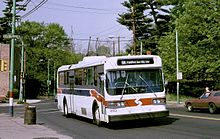 On the roof of the white trackless trolley, two poles rise up to contact overhead wires. A red stripe wraps around the front quarter of the vehicle continuing as a blue stripe on the side.