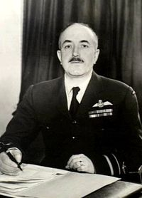 Half-length portrait of mustachioed man in military uniform with pilot's wings on left breast pocket, seated at desk with pen and papers