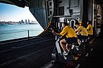 Sailors conduct their bi-annual Physical Readiness Test on stationary bikes in the hangar bay. (34002452244).jpg