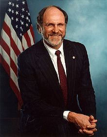 Head and shoulders of a man in his mid-fifties, seated with hands clasped. He is Caucasian and wears glasses and a black suit with a white dress shirt and a red tie. His head is balding and he has a gray beard with traces of brown hair. A U.S. flag is in the background.