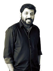 Upper-body photo of smiling man with dark hair, mustache and beard wearing dark-colored button down shirt